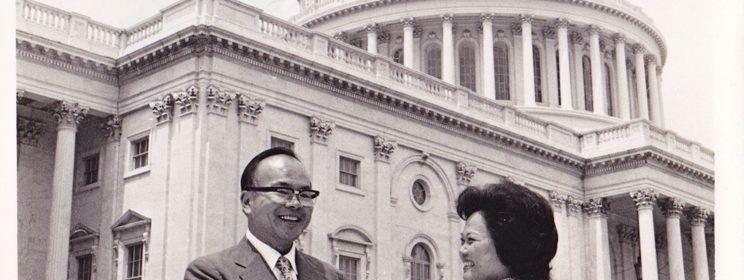 Black and white photo of Sam Lee outside the U.S. capitol shaking hands with Patsy T. Mink. Signed by Mink, to Lee.